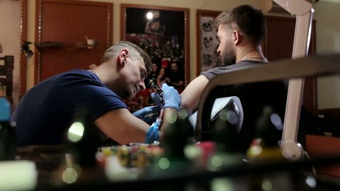 A young man is tattooing a bearded guy in a fashionable tattoo parlor. Master tattoo artist with a beard makes tattoo. Close-up. Tattoo shop.