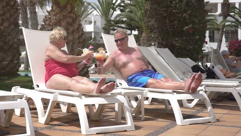 High quality video of happy senior couple drinking cocktails on the sunbeds in real 1080p slow motion 250fps