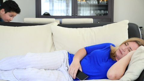 Young gamer boy filching mother's smart phone, when she sleeping on sofa at home