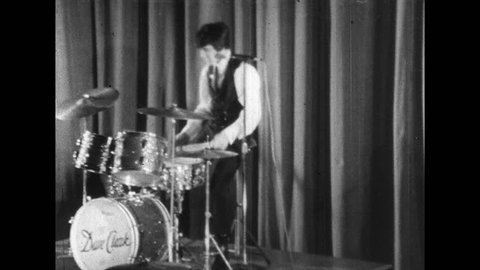 1960s: Man plays drums while on stage. Woman in crowd screams. Women in crowd dance. Woman in crowd gyrates her head.