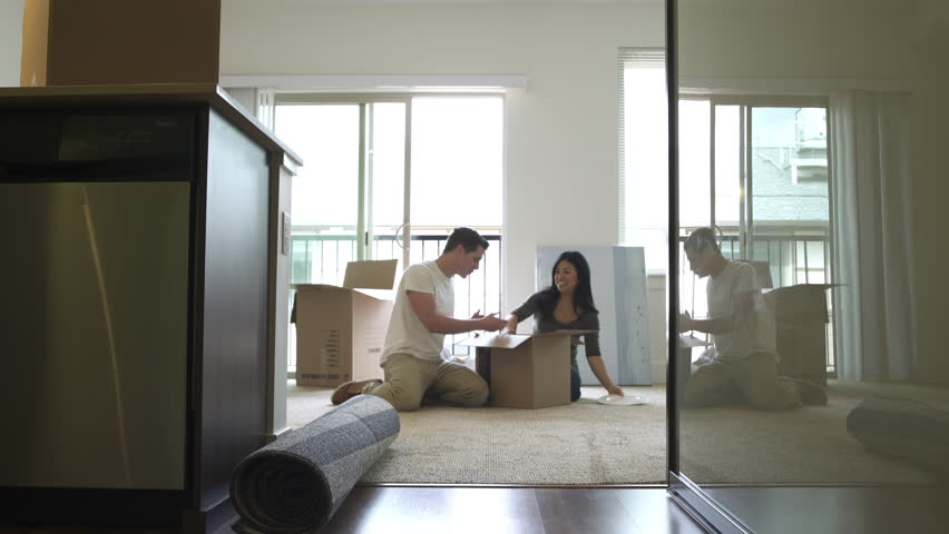 Wide shot of a couple unpacking a cardboard box | Shutterstock HD Video #1011000425