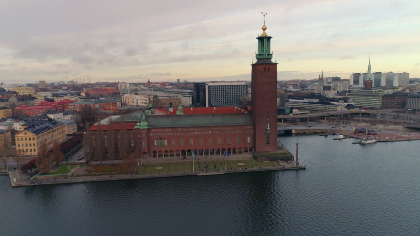 Stockholm City Hall aerial view. Drone shot flying around Stockholm Town Hall, famous landmark in the Capital of Sweden. Nobel Prize building, cityscape in the background