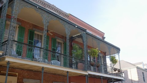 Establishing shot of a victorian balcony in the French Quarter of New Orleans. The breezy wrought iron veranda of the townhouse overlooks the esplanade where partygoers celebrate Mardi Gras.