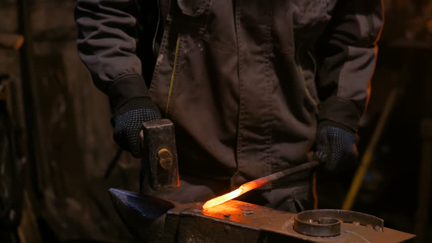 Professional blacksmith forging molten metal on anvil at smithy, workshop. Handmade, craftsmanship and blacksmithing concept