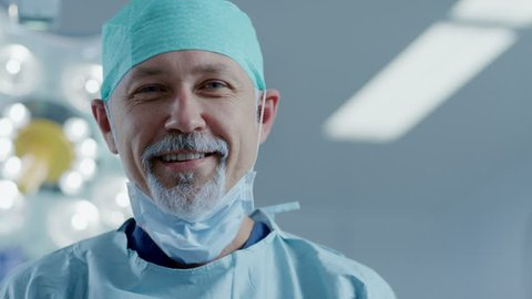 Portrait of the Professional Surgeon Taking off Surgical Mask after Successful Operation. In the Background Modern Hospital Operating Room. Shot on RED EPIC-W 8K Helium Cinema Camera.