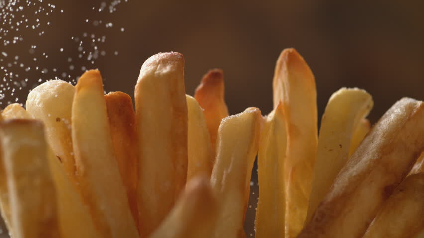 Adding salt on french fries. Shot with high speed camera, phantom flex 4K. Slow Motion. | Shutterstock HD Video #1011040595