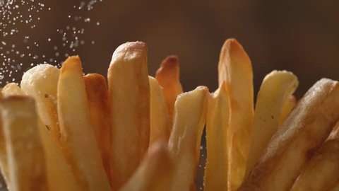 Adding salt on french fries. Shot with high speed camera, phantom flex 4K. Slow Motion.