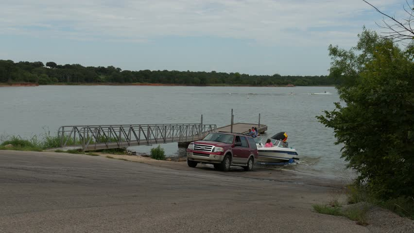 NORMAN, OKLAHOMA—AUGUST 2017:  Steady shot of an SUV towing a boat out of the water in Thunderbird Lake.