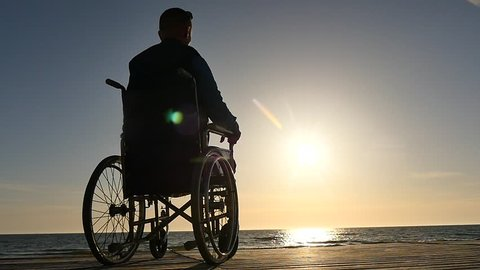 disabled man in wheelchair near sea coast panoramic shot silhouette