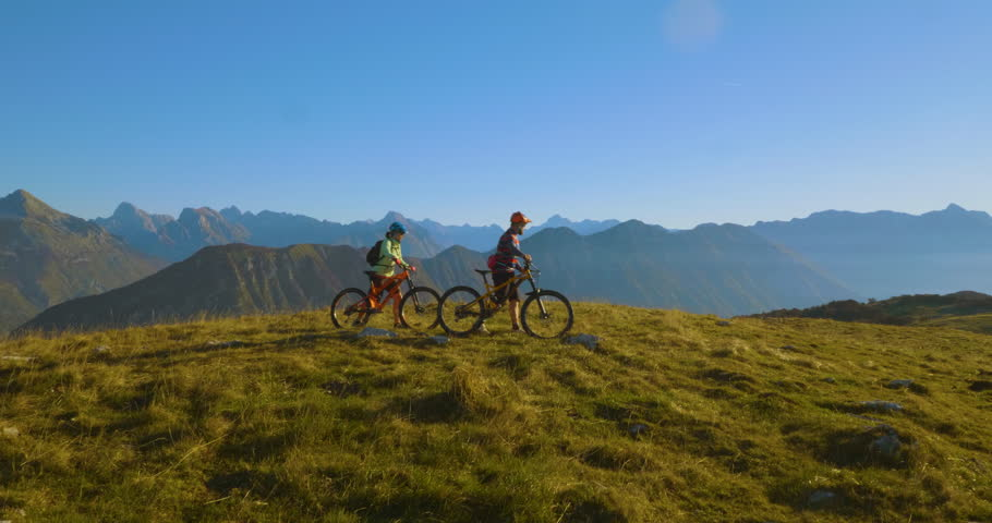 Aerial shot of mountain bikers on the top looking at amazing view in the summer.