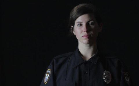 Female police officer against a black backdrop