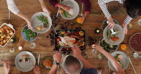 top view of family preparing table enjoying delicious vibrant thanksgiving meal dad cutting Turkey together tasty homemade lunch in festive season time lapse close up