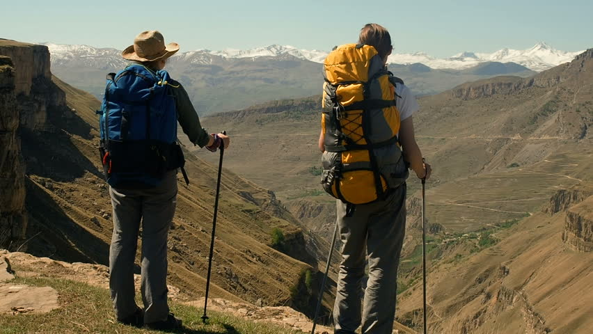 Hiking People Trekking On Trail. Woman and man hikers walking during trekking hike in summer. Backpackers Hiking In Mountains.    Shutterstock HD Video #1011124235