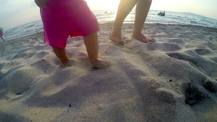 Undefined baby feet walking on beach at sunset with mother holding his hand
