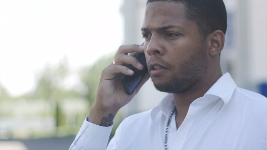 African American man aggressively communicates by phone | Shutterstock HD Video #1011149375