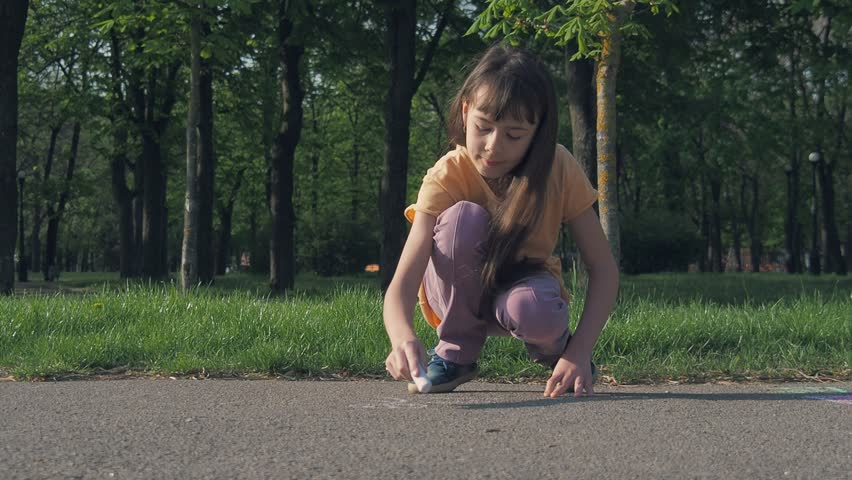 The child draws in the park. The girl draws chalk on the asphalt.