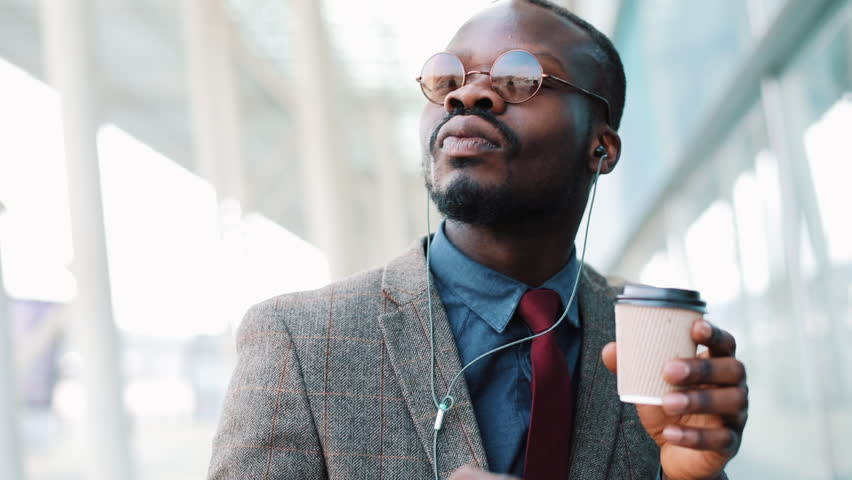 Happy african american businessman listening to music in headphones on smartphone, walking outside the office and funny dancing to the rythm. Drink coffee, funny dancing moves. Close up, slow motion #1011169145