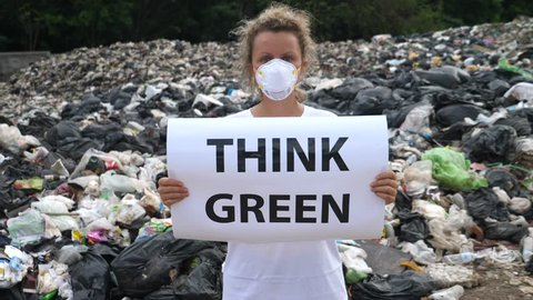 Young Woman Holding 'Think Green' Poster At Garbage Dump. Overconsumption.