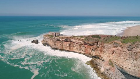 Flight near Rock and Lighthouse near City of Nazare, a very famous place for surfers