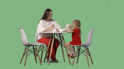 Mather with the little daughter are sitting at the table and drink a tea. Green screen footage. File format - .mov, codec PNG+Alpha. 85 mm lens