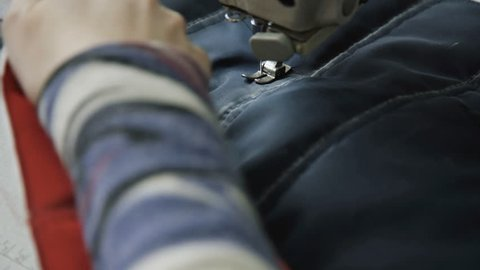 Close up process of sewing sheepskin coat with sewing machine. 4K.