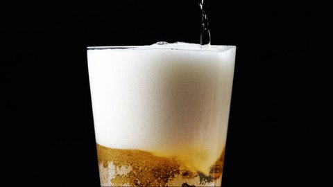 A mug of beer on a black background rotates. beer small bubbles slowly rise.