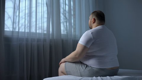 Obese male stretching shoulder muscles, orthopedic and rheumatologic disorders