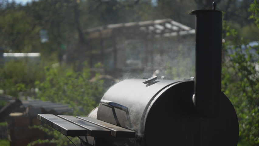 Smoke coming out from round metal smokehouse. | Shutterstock HD Video #1011223985
