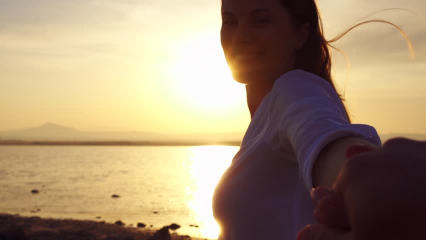 Young couple holding hands outdoors at golden hour at sunset. Happy woman in white shirt leading her boyfriend on lake in slow motion. Female traveler turning around and smiling. Follow me concept. #1011229295