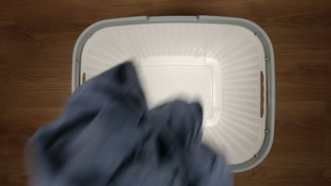 TOP VIEW: One dirty cloth falls to a laundry basket on a floor - Slow Motion