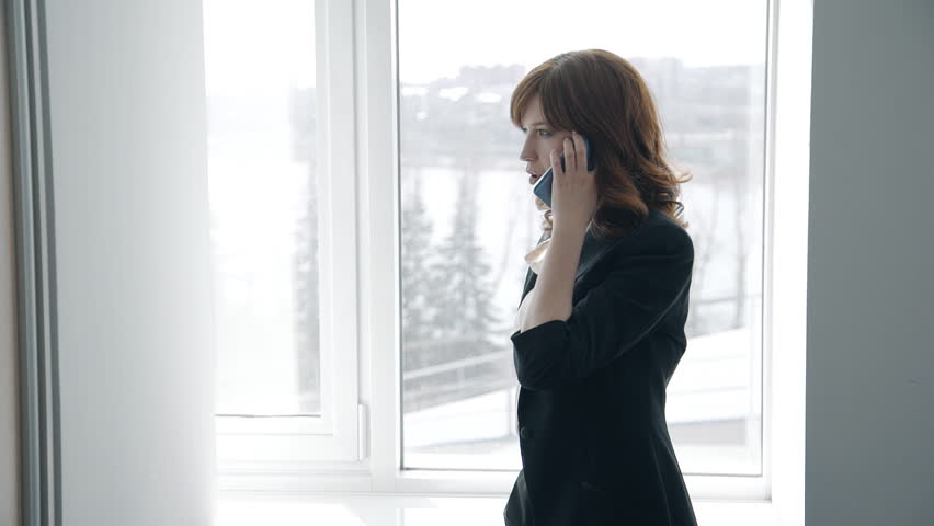 Attractive businesswoman is talking on phone by window in modern office, successful person making call, walking, discussing business in company. Concept: business conversation, professional