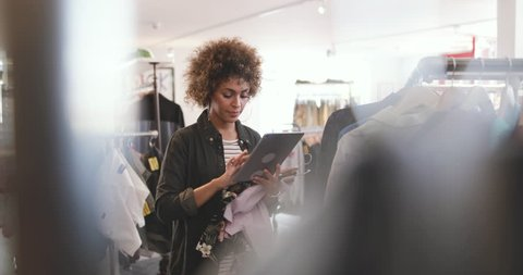 Store manager using digital tablet in a clothing store