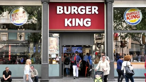 Barcelona, Spain - May 14, 2018: Burger King restaurant front on La Rambla street in Barcelona, with people passing by