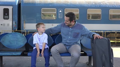 Father and son waiting in train station, big luggage, ready for a adventure trip