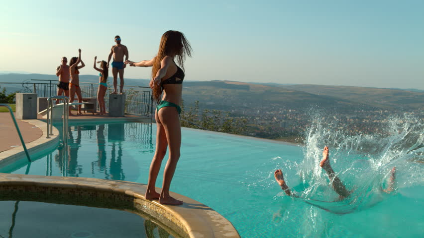 Woman pushing a man in the pool at a party | Shutterstock HD Video #1011287585