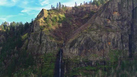 Drone aerial descending crane style shot of the massive moss covered cliffs at Crown Point revealing a small waterfall and lake at the bottom in the in the Columbia River Gorge at the end of winter