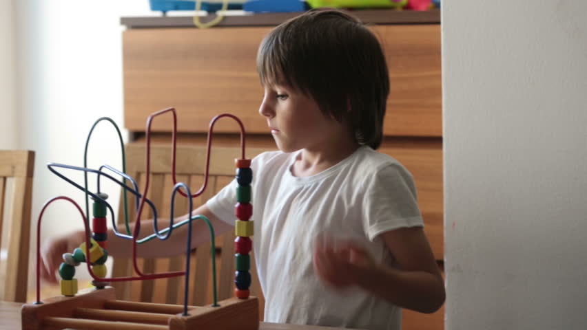 Preschool child, playing with toys in a sunny room, child development | Shutterstock HD Video #1011290315