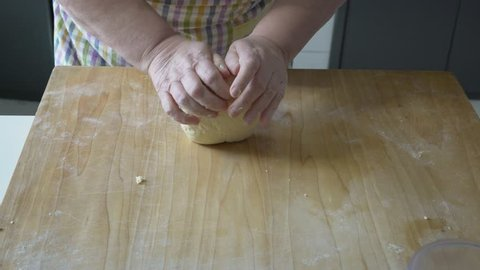 italian woman make homemade pasta gnocchi on wood board. Typical senior woman from south of Italy makes pasta from dough step by step.