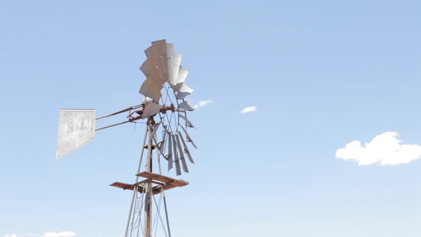 Windmill windpump pumping water as it spins in the dry arid region of the Tankwa Karoo of South Africa.
