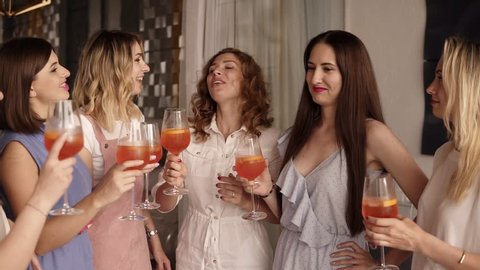 Six beautiful stylish women in elegant casual outfit celebrating and drinking alcohol cocktails. Cheers. Beautiful, modern interior. Hen party. Slow motion