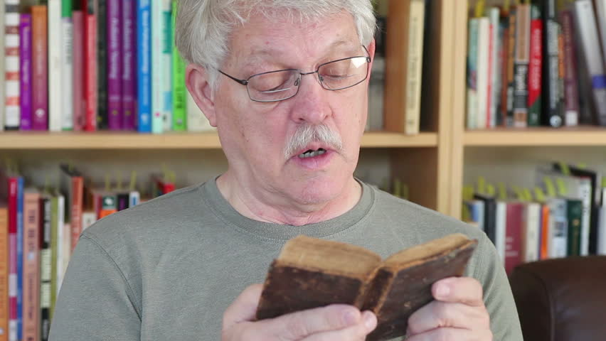Older man reads from well-used book of Psalms in front of a bookcase