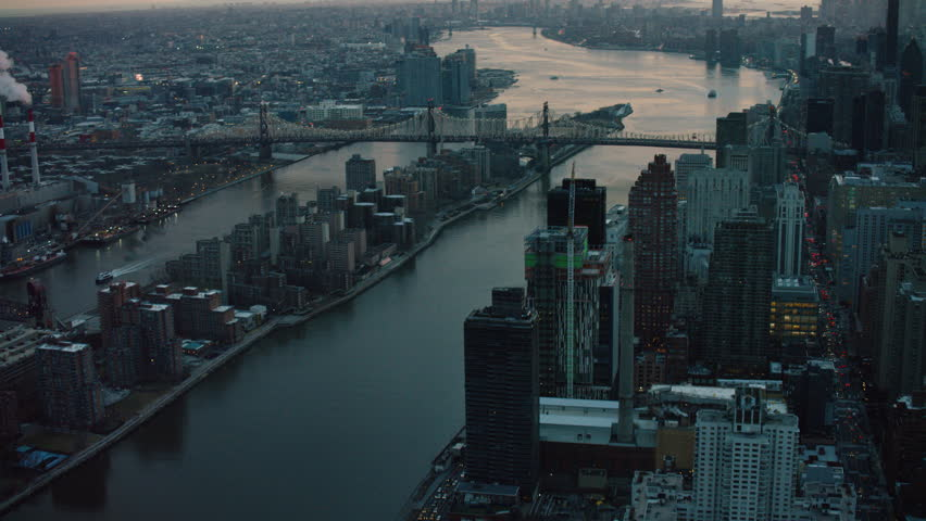 Aerial view of river and large city at sunset. Flying over skyscrapers and river in New York. Shot with a RED camera.
