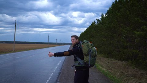 A tourist hitchhiker walks along the road with a backpack on his shoulders, lifting his thumb up. Traveler is trying to stop the car. The weather is cloudy and rainy.