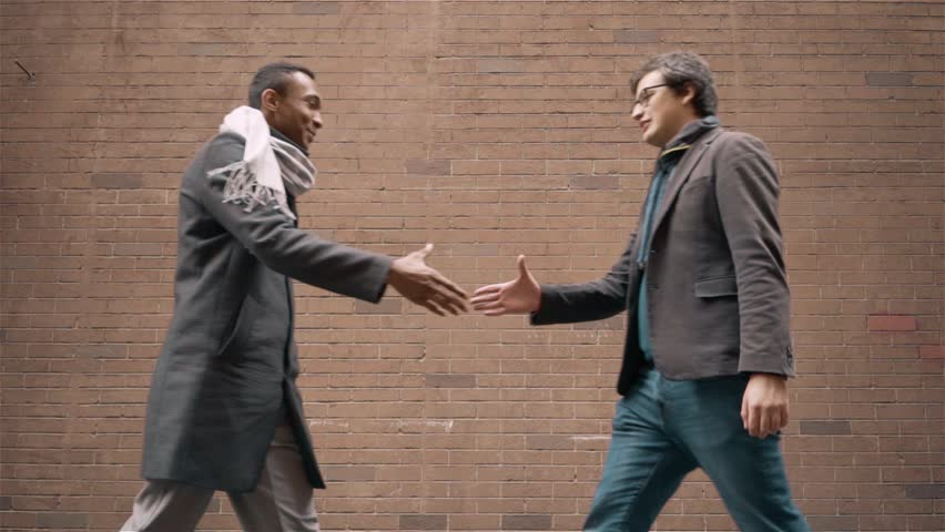Two young businessmen wearing coats and scarves meeting in the street and shaking hands. Ten talking. Concept of communication and friendship. Handheld slow motion medium shot