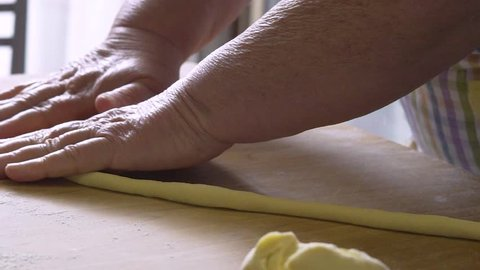 hands of woman making pasta gnocchi and orecchiette from dough process. typical italian food