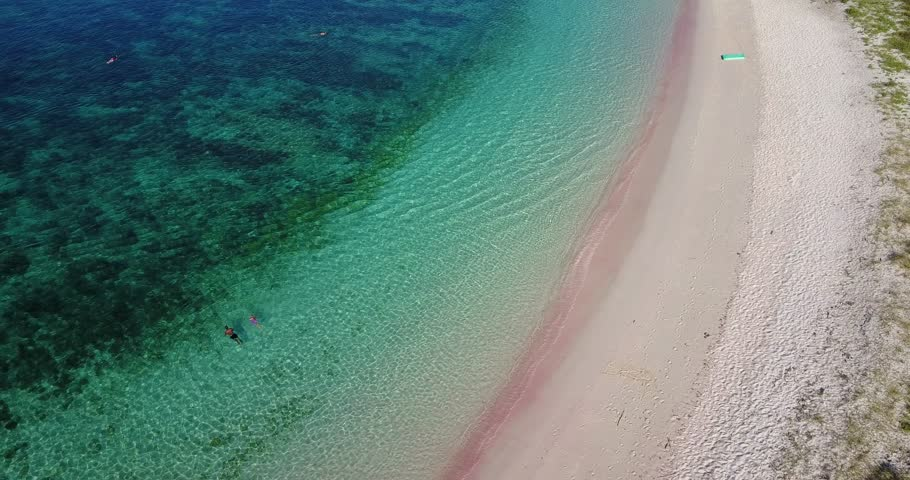 Beautiful top view footage of Pink Beach with a boat and pink sand in the Komodo National Park Island, Indonesia. Shot in 4k resolution | Shutterstock HD Video #1011348275