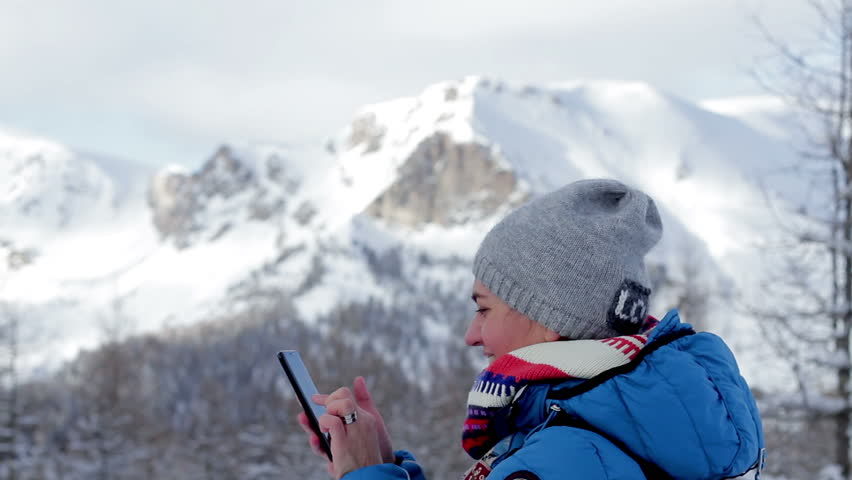 Attractive woman with her smartphone in the snowy mountains, Alps, Austria  | Shutterstock HD Video #1011361085