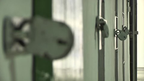 Close up rack focus across a large padlocks on prison cell or mental asylum facility doors
