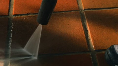 Closeup on cleaning outdoor floor ceramic tiles with high pressure water washer. Water sprinkling and shining in evening sunset. Spring cleaning arround the house.