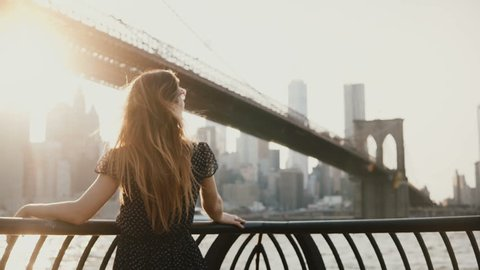 Back view of beautiful girl with flying hair leaning on river embankment fence at Brooklyn Bridge, looking at camera 4K.
